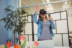 Businesswoman gesturing while using virtual reality headset Stock Photography