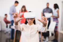 Businesswoman gesturing while using vr glasses. With colleagues in background Royalty Free Stock Image
