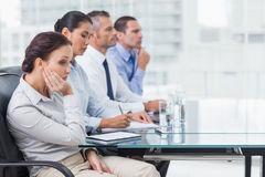 Businesswoman getting bored while attending presentation. Businesswoman in bright office getting bored while attending presentation royalty free stock photography