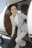 Businesswoman Getting Down From Airplane Stock Photography