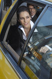 Businesswoman Getting Out Of Taxi Stock Photos