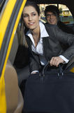 Businesswoman Getting Out Of Taxi Stock Photo