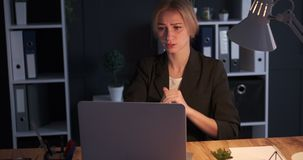 Businesswoman receiving bad news on laptop. Businesswoman getting upset after receiving bad news on laptop during night shift stock video