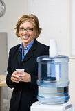 Businesswoman getting water from water cooler. Businesswoman getting water from a water cooler Stock Photos