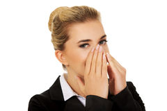 Businesswoman giggles covering her mouth with hand Royalty Free Stock Image