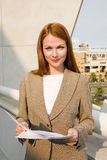 Businesswoman, with ginger hair, standing on balcony, holding document, smiling, front view, portrait Royalty Free Stock Photo