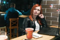 Businesswoman, girl working on laptop in cafe, smartphone, pen, use computer. Freelancer works remotely. Online marketing,. Education for adulte. Night city stock photo