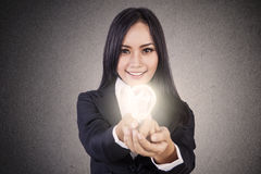 Businesswoman give lit lightbulb Stock Images