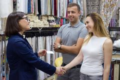 Businesswoman gives couple visit card shakes hands royalty free stock photography
