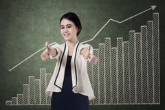 Businesswoman gives thumb up. Beautiful business woman gives thumb up with graph background stock image