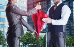 Businesswoman gives umbrella to businessman Royalty Free Stock Images