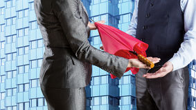Businesswoman gives umbrella to businessman Stock Photo