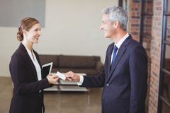 Businesswoman giving business card to client in office Stock Photos