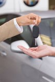 Businesswoman giving car key to happy customer. At new car showroom Royalty Free Stock Photography