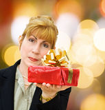 Businesswoman giving gifts on a special day. Businesswoman gives a gift for the celebration of a special day. Over defocused lights stock photography
