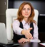 Businesswoman giving handshake. In her office Stock Photography
