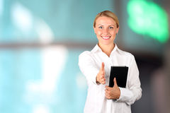 Businesswoman giving a handshake on a blue background Stock Photography