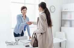 Businesswoman giving an handshake Stock Photo