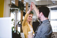 Businesswoman giving high-five to male coworker Royalty Free Stock Photo