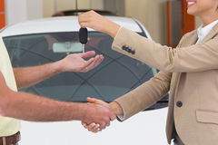 Businesswoman giving key while shaking a customer hand Royalty Free Stock Images