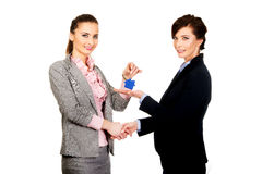 Businesswoman giving a key to her partner. Stock Images
