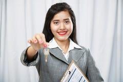 Businesswoman giving keys Stock Photo