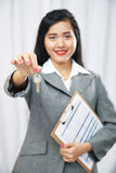 Businesswoman giving keys Royalty Free Stock Photos