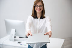 Businesswoman giving laptop on camera Stock Images