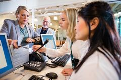 Businesswoman Giving Passport To Staff At Desk In Airport. Senior businesswoman giving passport to female staff at reception desk in airport Stock Images