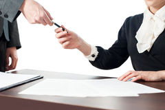 Businesswoman giving pen to colleague stock image