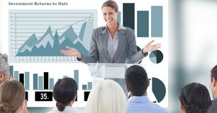 Businesswoman giving presentation to colleagues with graphs in background. Digital composite of Businesswoman giving presentation to colleagues with graphs in Stock Photography