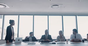 Businesswoman giving a presentation to her team stock footage