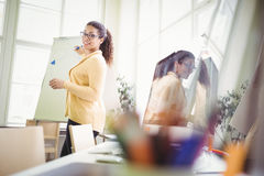 Businesswoman giving presentation on whiteboard in creative office Stock Photo