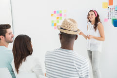 Businesswoman giving presenting in front of group Stock Photos