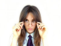 Businesswoman with glasses. Portrait of young businesswoman with long hair peering over glasses; white studio background royalty free stock photo