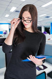 Businesswoman in glasses with folder. Portrait of attractive businesswoman in glasses with blue folder royalty free stock photos