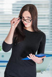 Businesswoman in glasses with folder. Portrait of attractive businesswoman in glasses with blue folder royalty free stock photography