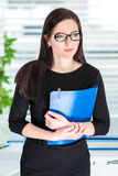 Businesswoman in glasses with folder. Portrait of attractive businesswoman in glasses with blue folder royalty free stock photo