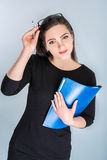 Businesswoman in glasses with folder. Portrait of happy businesswoman in glasses with blue folder on blue background top view stock photography