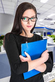 Businesswoman in glasses with folder. Portrait of happy smiling businesswoman in glasses with blue folder royalty free stock images