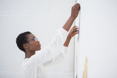 Businesswoman with glasses pinning paper up Stock Photography