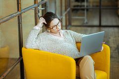 Businesswoman wearing sweater and glasses while working on laptop stock photos
