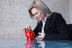 Businesswoman in glasses put coins into red dotted piggy bank Royalty Free Stock Photos