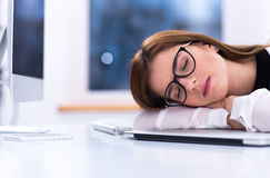 Businesswoman in glasses sleeping at her workplace Royalty Free Stock Image