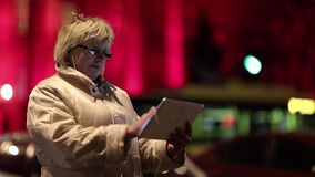Businesswoman with glasses stands near the road and uses Tablet PC. Senior woman with Tablet-PC stands near the road and red building in nighttime. Businesswoman stock video footage