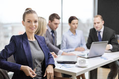Businesswoman with glasses with team on the back Royalty Free Stock Image