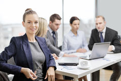 Businesswoman with glasses with team on the back Stock Photography