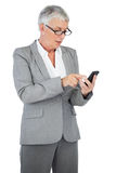 Businesswoman with glasses texting a message on her mobile phone Stock Photo