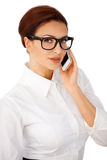 Businesswoman in glasses using a mobile. Attractive young brunette businesswoman in heavy framed glasses using a mobile phone isolated on white Stock Photography