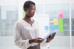 Businesswoman with glasses using tablet Stock Photography